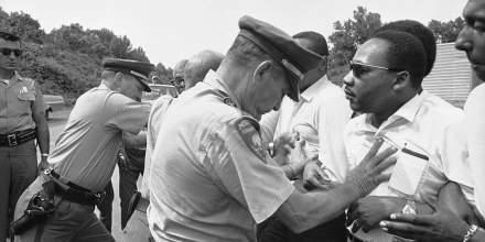 Mississippi Highway Patrolmen shove the Rev. Martin Luther King and members of his marching group off the traffic lane of Highway 51 south of Hernando, Miss., June 7, 1966. The Rev. King, Student Non-Violent Coordinating Committee leader Stokely Carmichael (head visible at upper right) and other civil rights leaders had taken up the march begun by James Meredith. (AP Photo)