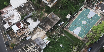 PUERTO RICO - OCTOBER 18:  People play volleyball (TOP R) next to damaged buildings during recovery efforts four weeks after Hurricane Maria struck on October 18, 2017 in-flight over Puerto Rico. Puerto Rico is suffering shortages of food and water in areas with only 19.10 percent of grid electricity restored. Puerto Rico experienced widespread damage including most of the electrical, gas and water grid as well as agriculture after Hurricane Maria, a category 4 hurricane, swept through.  (Photo by Mario Tama/Getty Images)