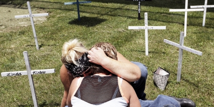 Kelli Lane, top, hugs Mary Randol before writing the name of Randol's son Dustin Billings on a cross during the Madison County Making a Stand Against Heroin Benefit Ride on Saturday, June 24, 2017, in Anderson, Ind. Billings died of a heroin overdose in March 2016. Proceeds from the ride were given to the family of Carissa Horton to help pay for her funeral after she died from a heroin overdose in May. (Don Knight/The Herald-Bulletin via AP)