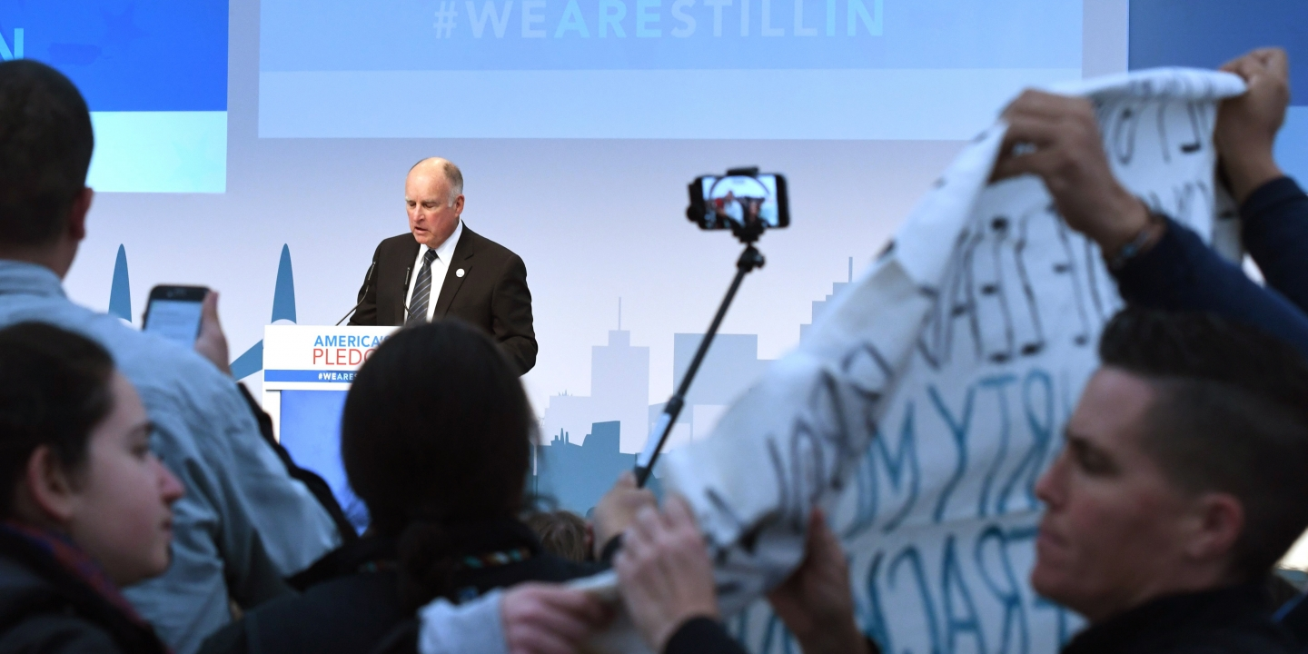 Protesters show banners and protest during the speech of US Governor of California, Jerry Brown at the launch event at the US climate action center on November 11, 2017 during the COP23 United Nations Climate Change Conference in Bonn, Germany. / AFP PHOTO / PATRIK STOLLARZ        (Photo credit should read PATRIK STOLLARZ/AFP/Getty Images)