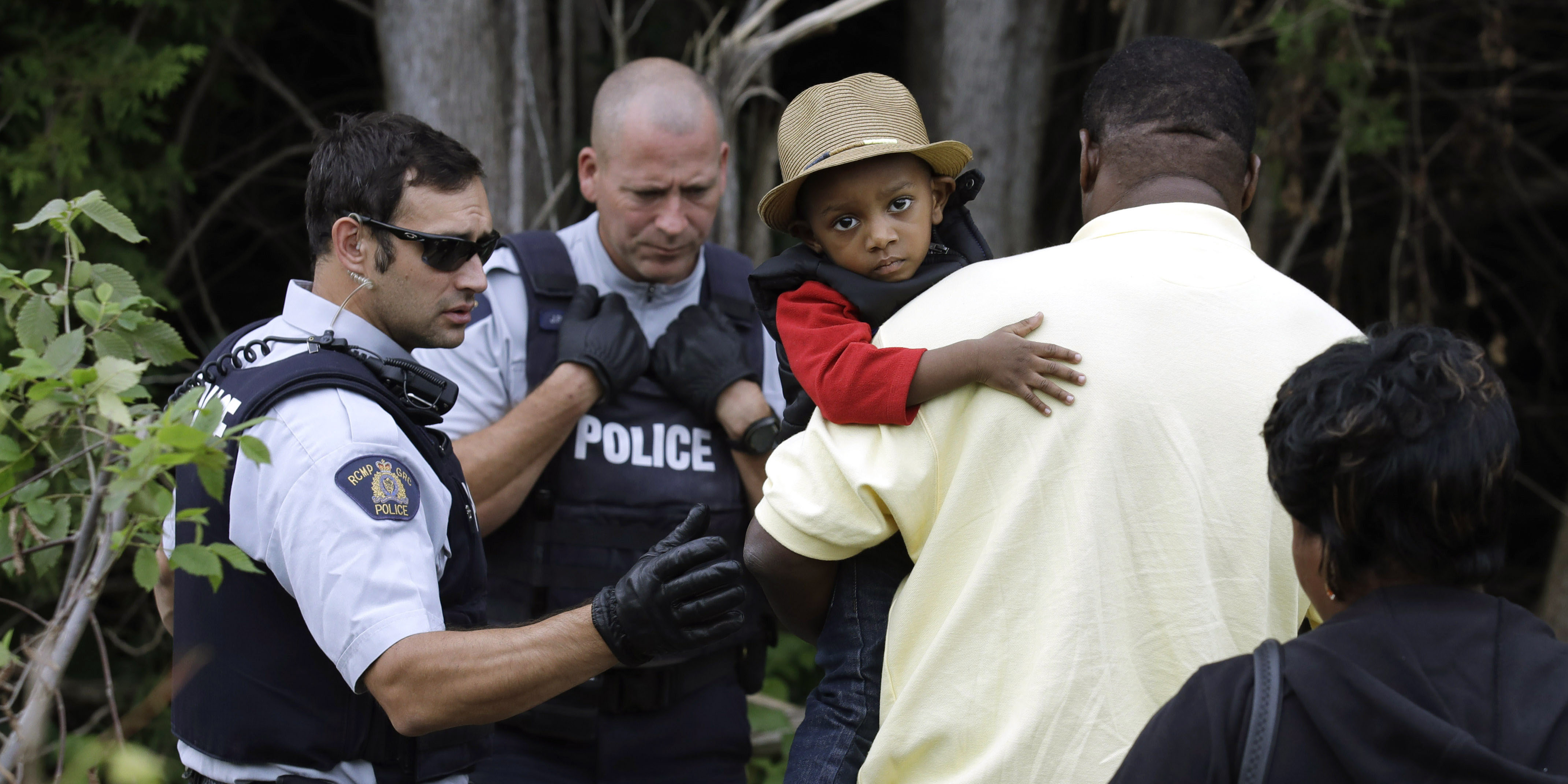 A Haitian boy holds onto his father as they approach an illegally crossing point, staffed by Royal Canadian Mounted Police officers, from Champlain, N.Y., to Saint-Bernard-de-Lacolle, Quebec, Monday, Aug. 7, 2017. Seven days a week, 24-hours a day people from across the globe are arriving at the end of a New York backroad so they can walk across a ditch into Canada knowing they will be instantly arrested, but with the hope the Canadian government will be kinder to them than the United States. (AP Photo/Charles Krupa)