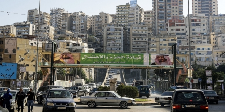 A picture taken on November 10, 2017 shows a banner bearing the images of Saudi King Salman bin Abdulaziz (R) and Crown Prince Mohammed bin Salman (L) hanging on a pedestrian crossing bridge in the northern Lebanese port city of Tripoli, between them a caption reading in Arabic