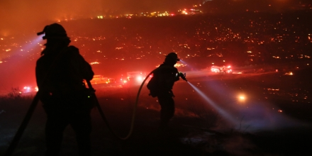 TOPSHOT - Firefighters walk to the fire line at the Lilac fire in Bonsall, California on December 7, 2017.Local emergency officials warned of powerful winds on December 7 that will feed wildfires raging in Los Angeles, threatening multi-million dollar mansions with blazes that have already forced more than 200,000 people to flee. / AFP PHOTO / Sandy Huffaker (Photo credit should read SANDY HUFFAKER/AFP/Getty Images)
