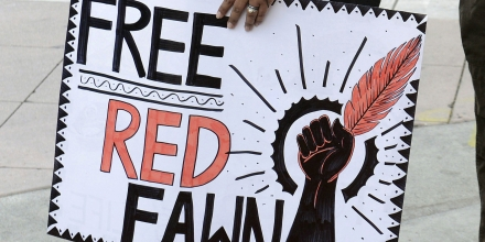 Protester Danielle Giagnoli carries a sign to free Red Fawn Fallis as she stands among a small group of protesters gathered for the