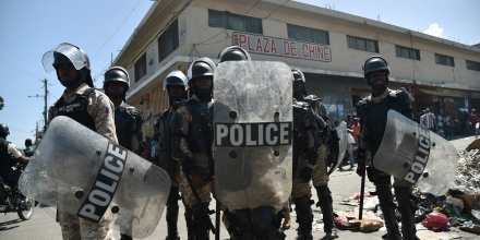 Police watch as demonstrators march to protest against the government of Haitian President Jovenel Moise in Port-au-Prince October 24, 2017. / AFP PHOTO / HECTOR RETAMAL        (Photo credit should read HECTOR RETAMAL/AFP/Getty Images)