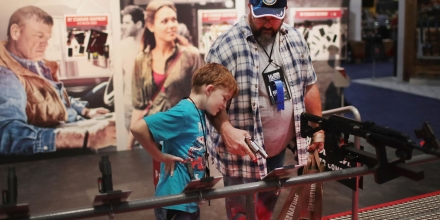 ATLANTA, GA - APRIL 29:  Andrew Farris and his son Eli look over guns fitted with Crimson-Trace sights at the 146th NRA Annual Meetings & Exhibits on April 29, 2017 in Atlanta, Georgia. With more than 800 exhibitors, the convention is the largest annual gathering for the NRA's more than 5 million members.  (Photo by Scott Olson/Getty Images)
