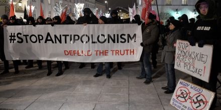 Far-right protesters hold a banner during a demonstration to support a controversial new Polish bill regarding the Holocaust and the definition of Nazi death camps on February 5, 2018 outside the presidential palace in Warsaw. The placards (R) read